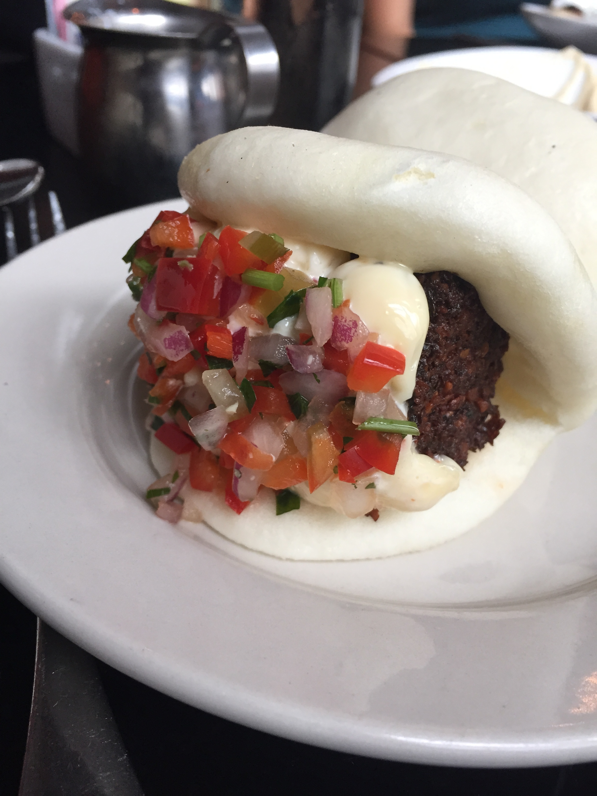 Falafel and hummus on a soft bun with peppers, onions, and tomatoes from  Mezetto .