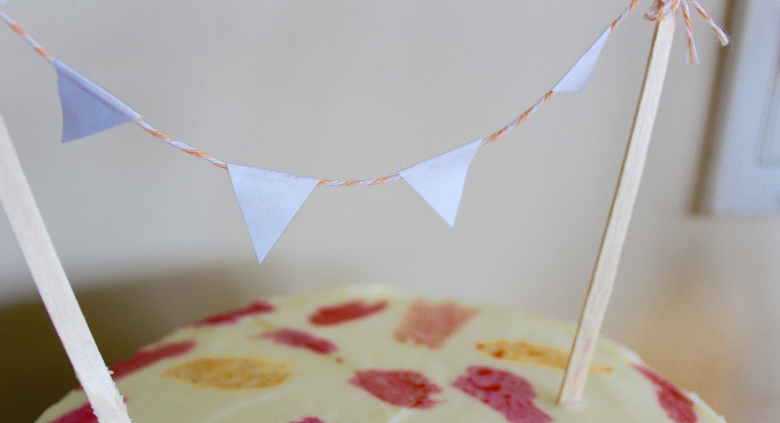 To make this bunting banner I took 2 coffee stirrers I had swiped from Starbucks and tied a small piece of embroidery floss between them. I cut out little triangles of white paper and glued them onto the floss.