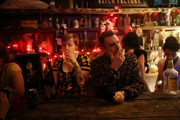 Duke Riley, right, enjoyed the last night's festivities at a speakeasy in Greenpoint, Brooklyn, on Saturday.  KIRSTEN LUCE FOR THE NEW YORK TIMES