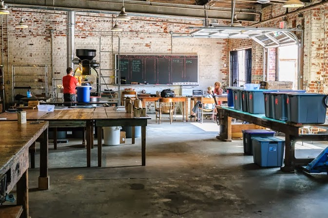 The complete renovations, with (from left to right) the large factory table / espresso bar, our long reclaimed heart pine tables with Victorian porch wood trim, long reclaimed wood tables, and our massive industrial L-beam table with salvaged stunning shattered glass tabletop.