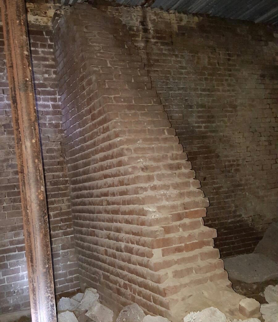 Two exposed sections of the subterranean brick wall, likely how they've been for over a century.