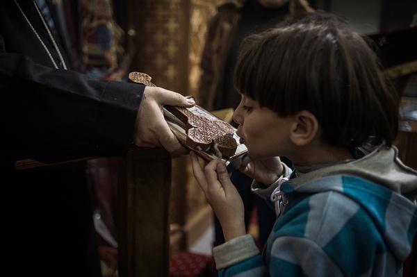 """2014年1月6日,埃及开罗,一名少年在科普特东正教""""平安夜""""弥撒上亲吻神父手中的十字架。"""