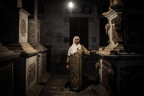 """2013年12月12日,埃及开罗""""死人城"""",一名妇女在其生活的墓室内留影。"""
