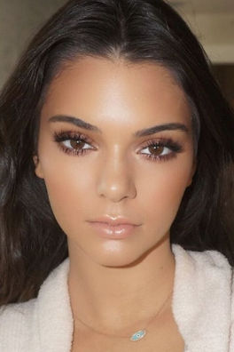 Kendall Jenner beaming with a natural looking bronzey glow, simple full lashes, bold brows & a glossy pout