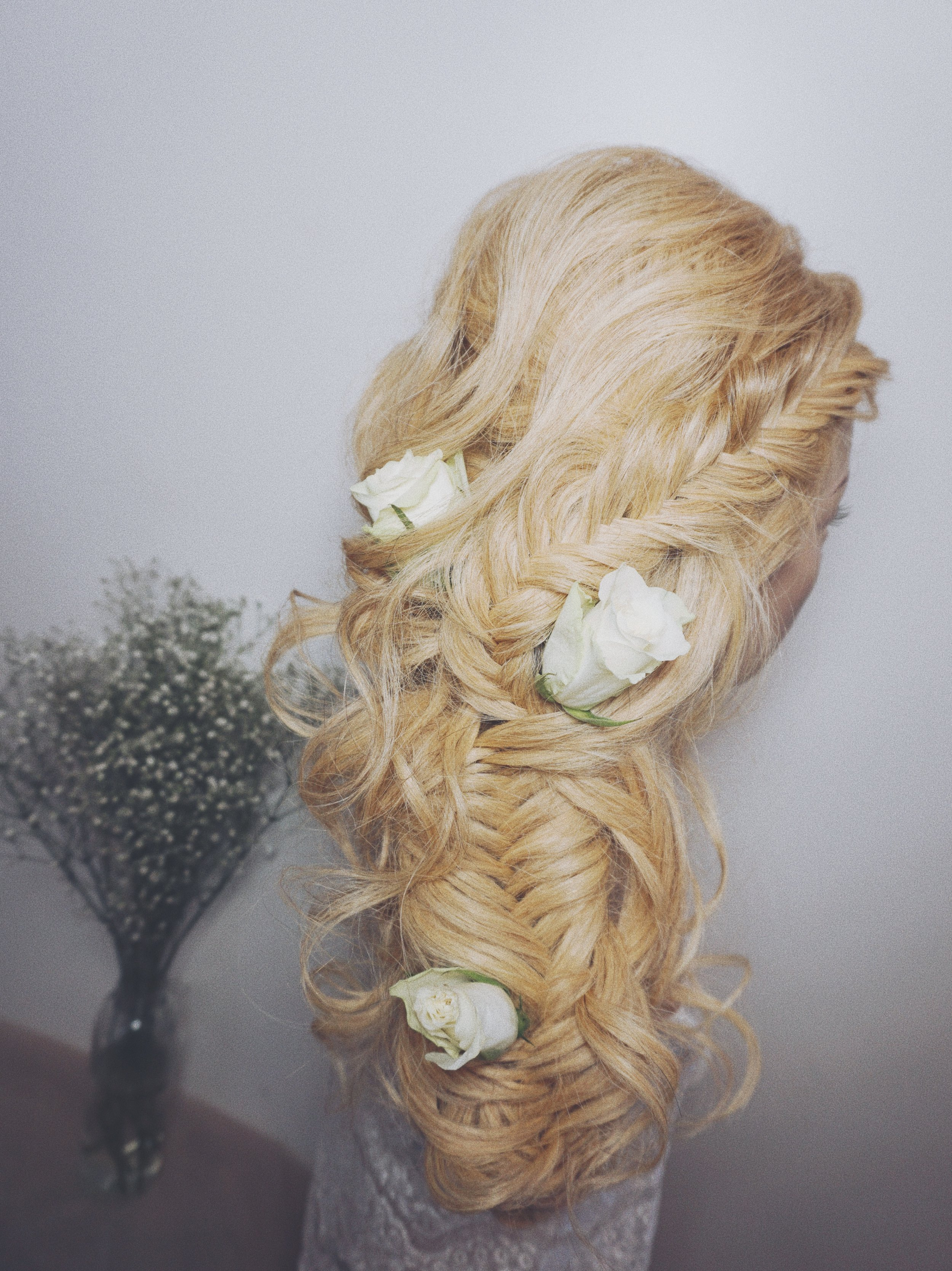 down the side fishtail braided wedding hairstyle idea with floral hair accessories