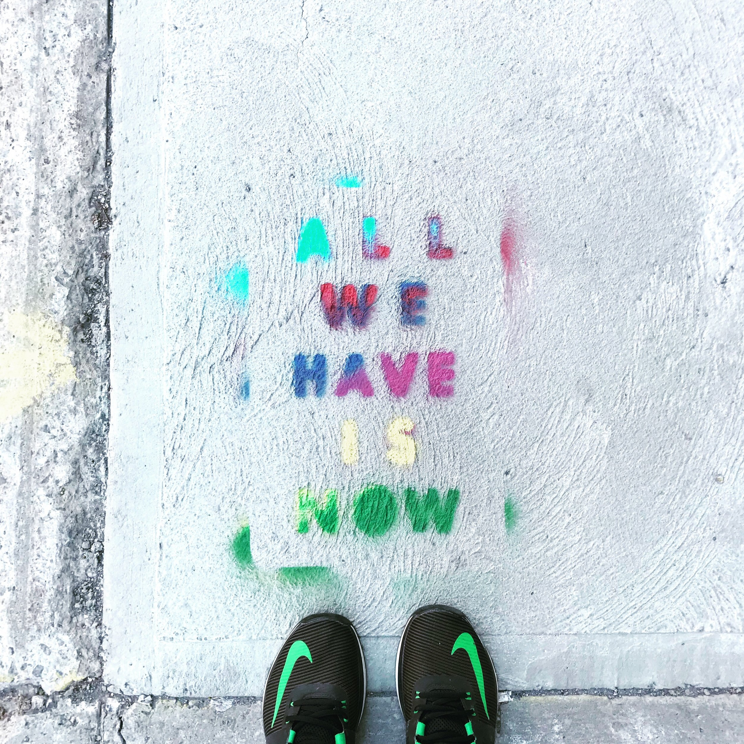 "A person views a spray painted colorful message on cement that says, ""ALL WE HAVE IS NOW."""