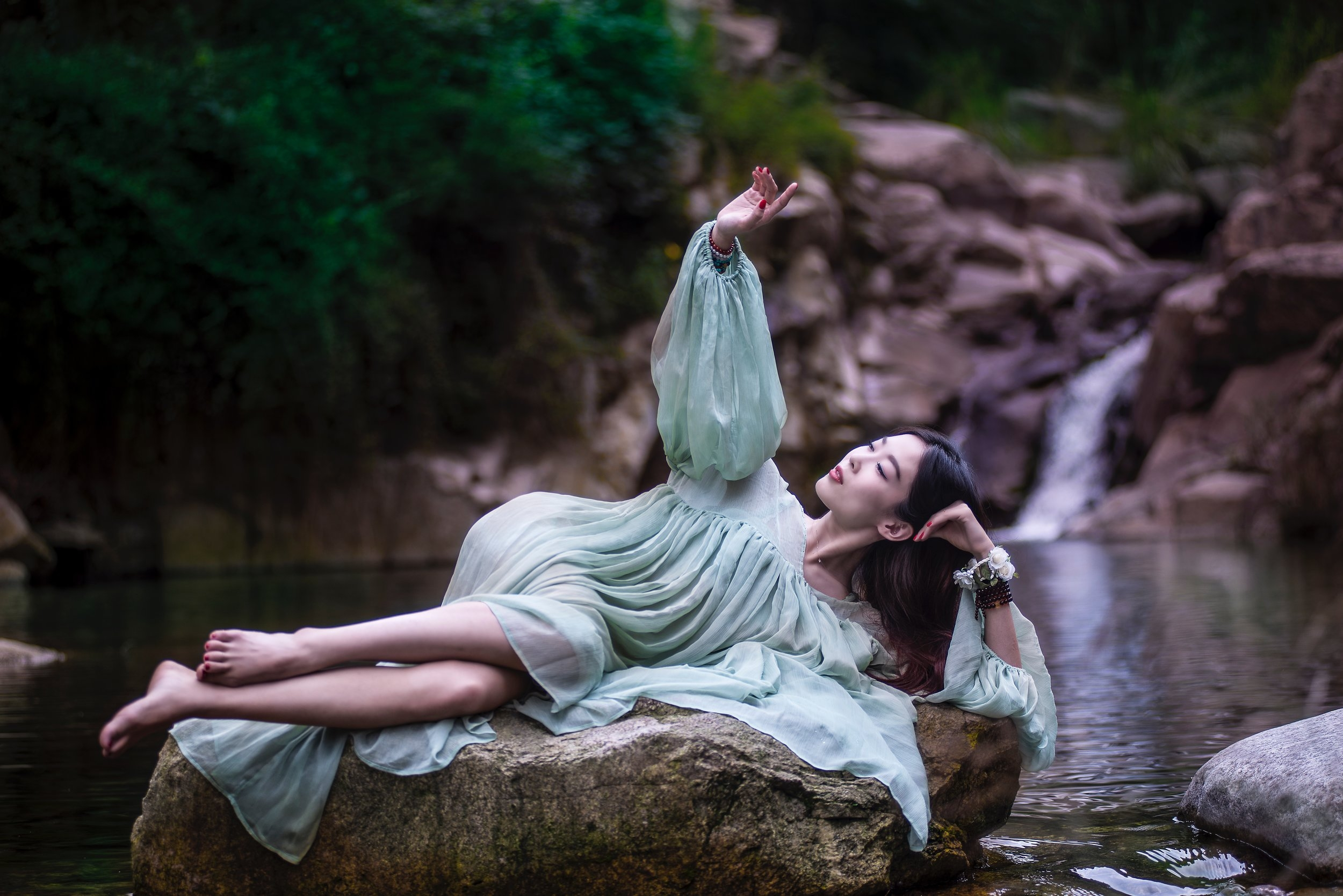 A young woman in a billowy gown relaxes reclining on a large rock before a waterfall