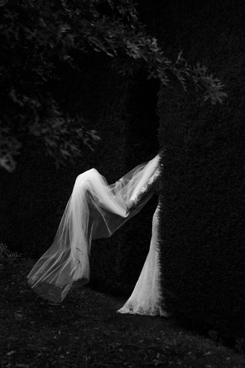 Bride walking through hedge at Mandalay House and Garden Wedding Dress Veil floating