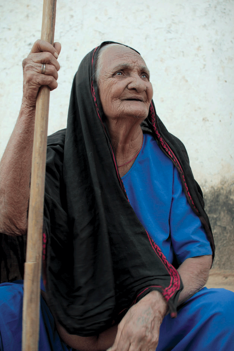 An elderly woman in Mundra wearing a veil cloth; the plain body with only a border design are specific to older women