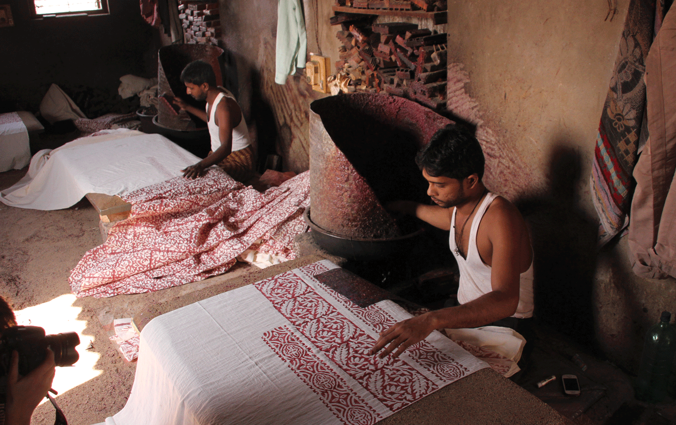 Batik printing is often done on low tables, on a surface of sand. The printer sits near the burner for easy access to the wax
