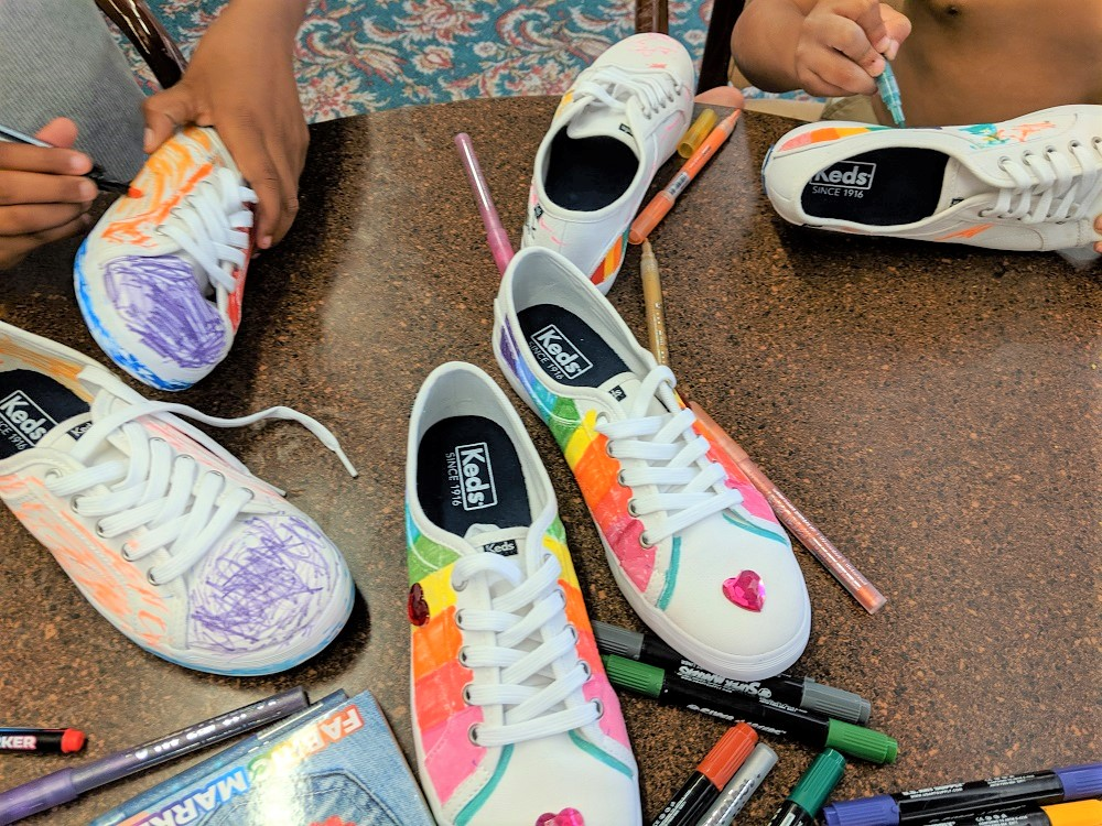 Children living at Fulton Manor decorated Keds shoes. Wolverine Wordwide will donate proceeds from sales of the shoes to the shelter.