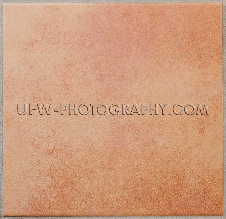 Single apricot colored ceramic tile textured full frame Stock Im