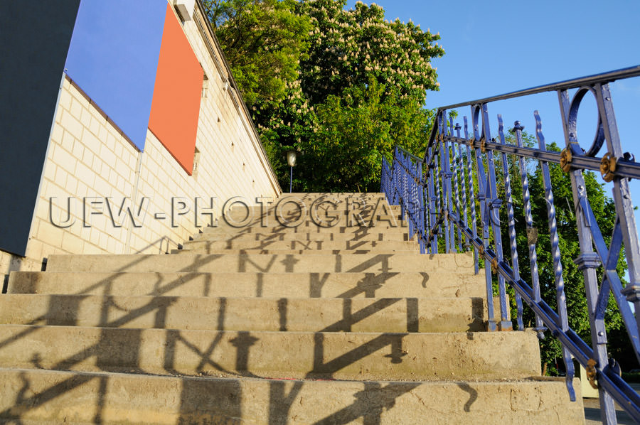 Ascending stone staircase, blue banister, clear sky, green chest