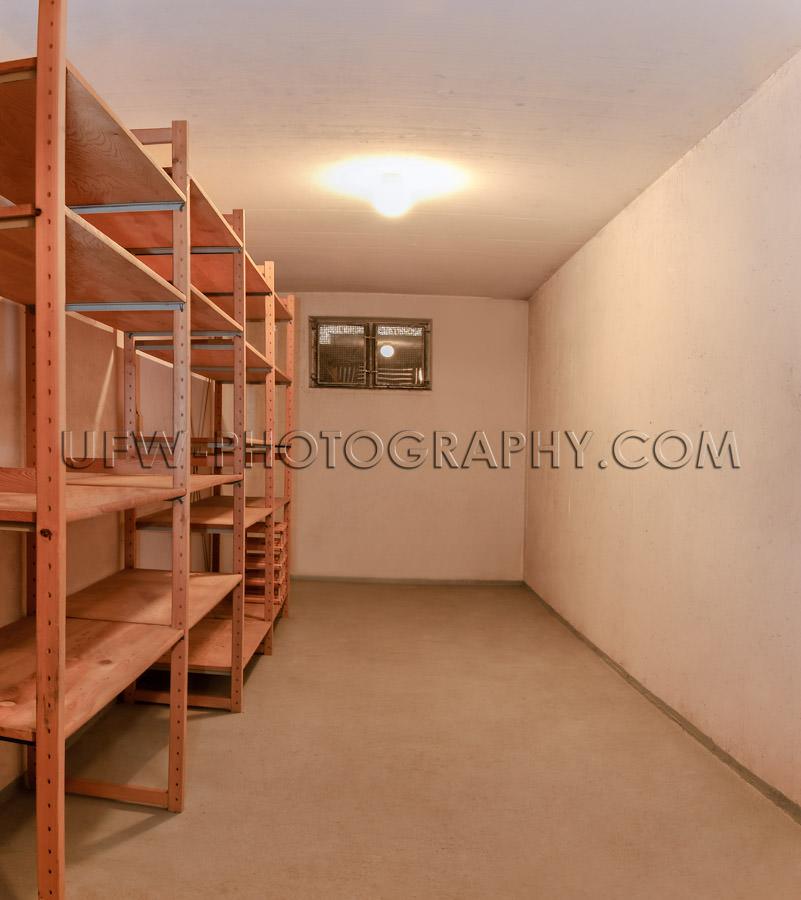 Empty basement room wooden storage shelve illuminated ceiling la