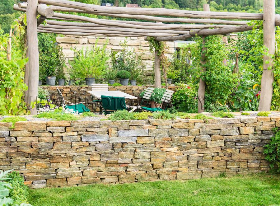 Idyllic garden scene gazebo outdoor furniture stone wall Stock I