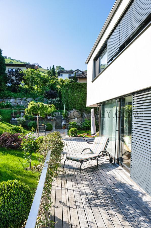 Modern detached house wooden deck deckchair green garden Stock I
