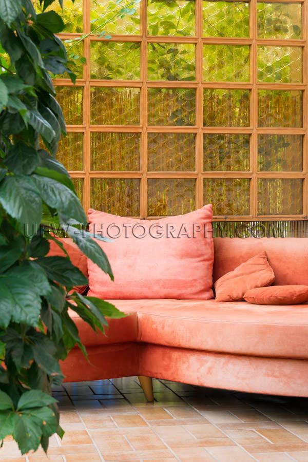 Patio cozy corner sofa orange plant tiled floor garden Stock Ima
