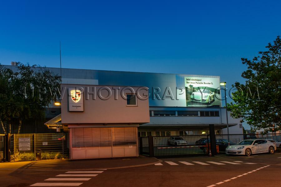 Porsche company headquarters gate car factory Germany night Stoc