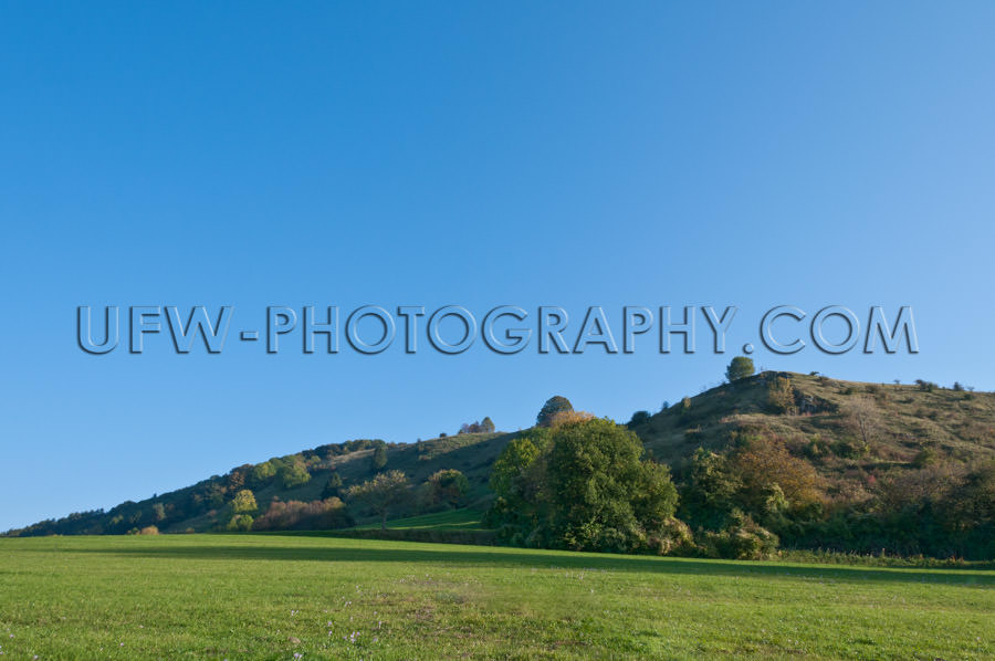 Gently rising hilly Landscape in autumn, against blue Sky - Stoc