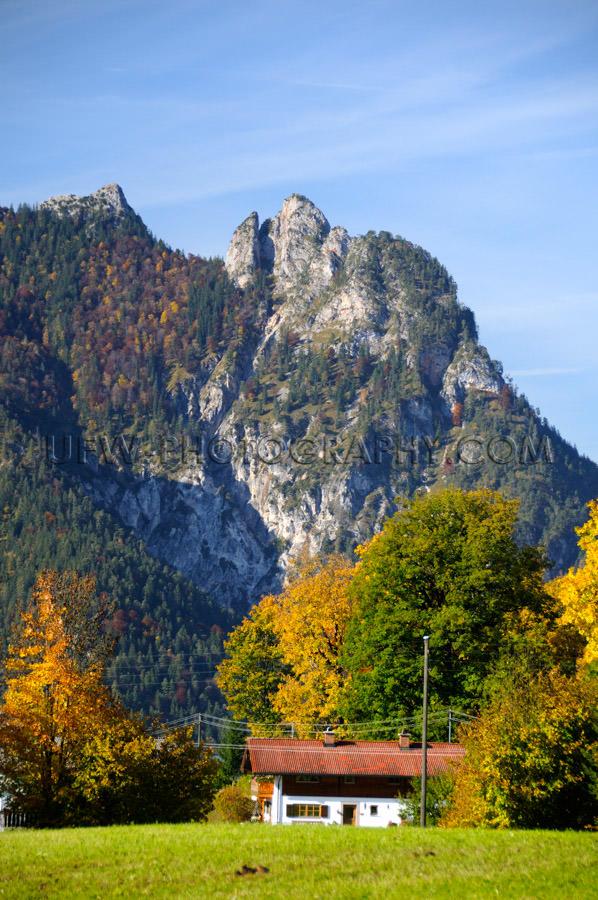 Idyllic farmhouse below witch mountain colorful fall trees Stock