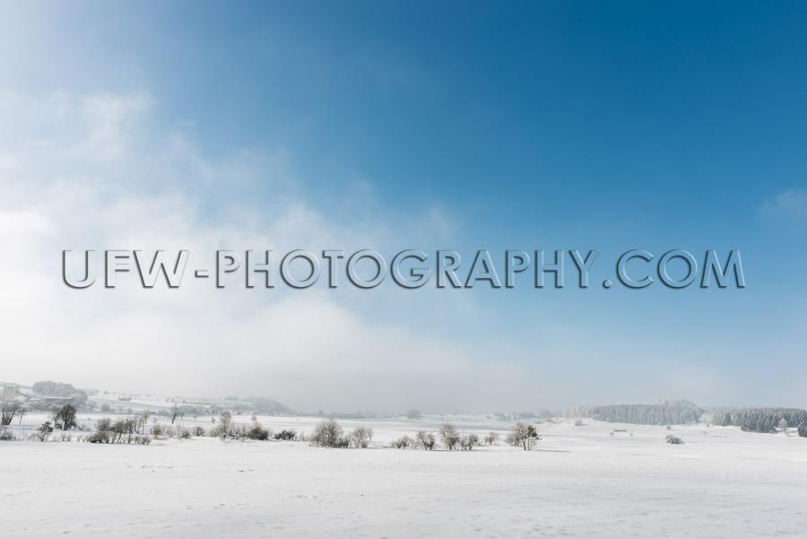 Idyllic winter scene snowy countryside trees blue cloudy sky Sto