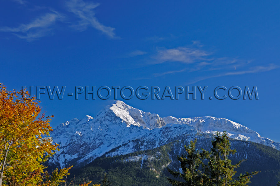 Mountain ridge with snowcapped peak against deep blue sky Stock