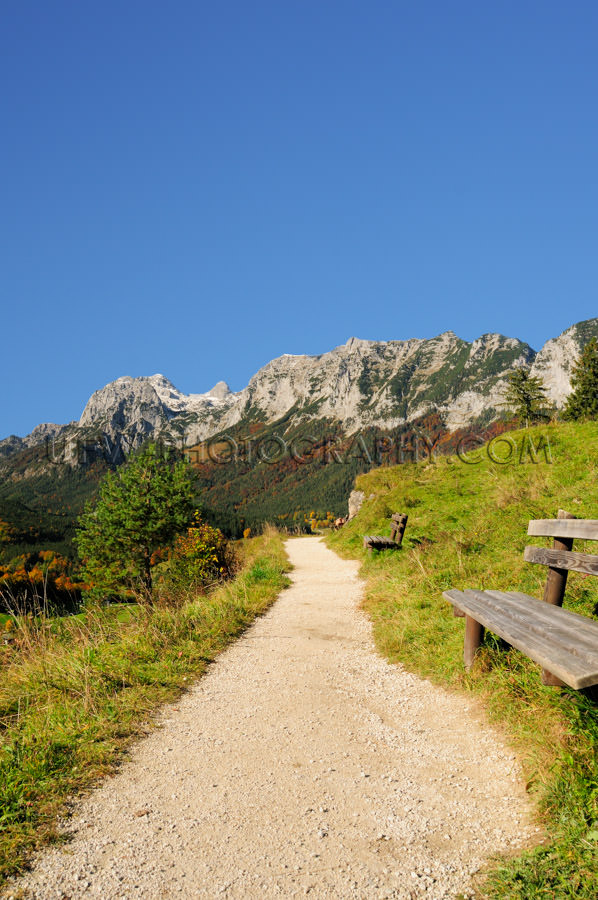 Sunny hiking trail in the mountains against deep blue sky Stock
