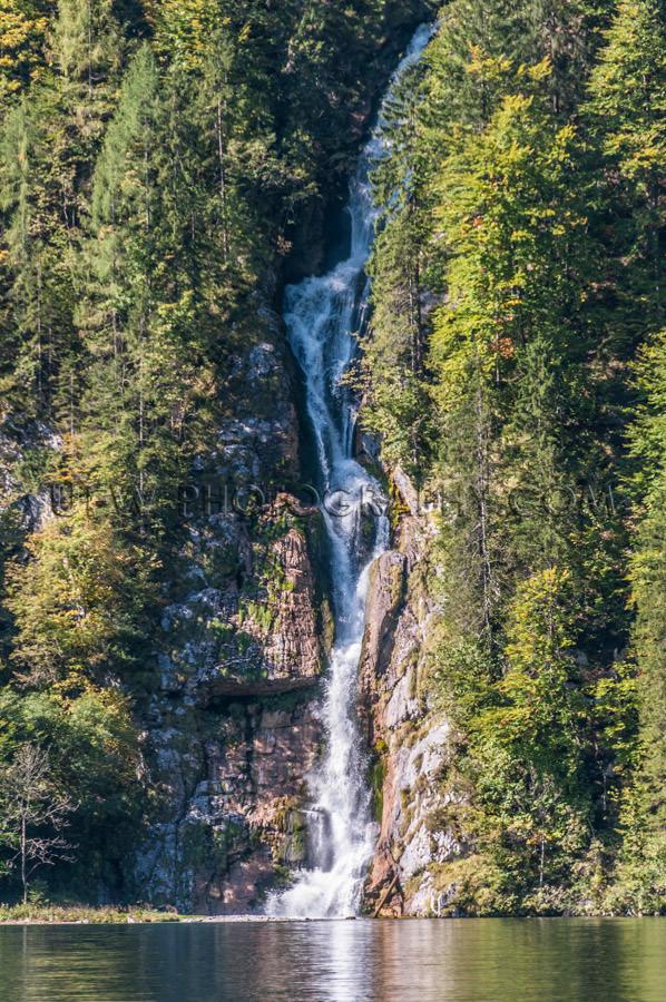 Waterfall steep cliff trees falling beautiful mountain lake Stoc