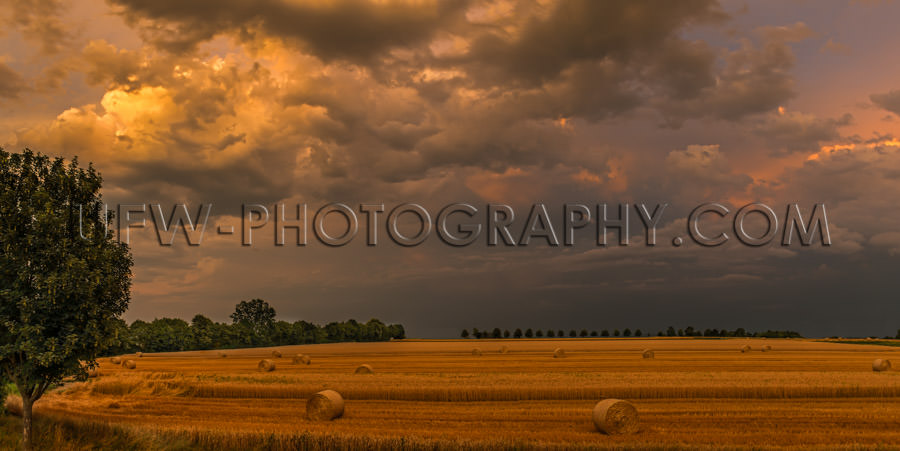 Autumn brown stubbles hay bales harvested field dark stormy sky
