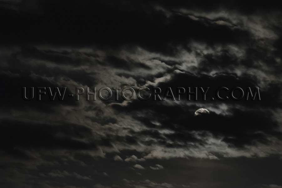 Full moon partly visible clouds dark moody mysterious night sky