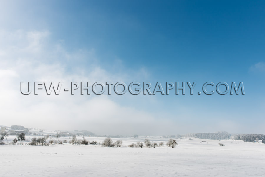 Idyllic winter scene snowy countryside trees blue cloudy sky Sto