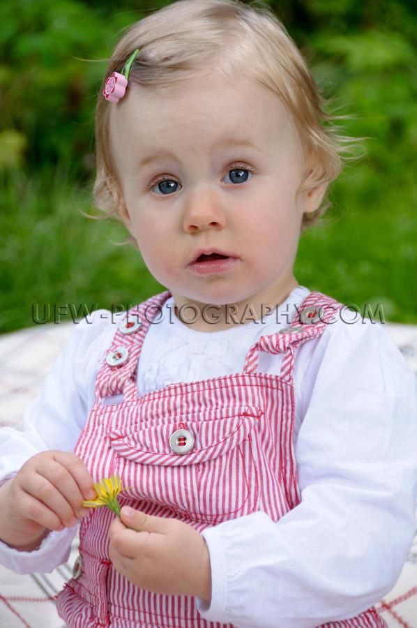Cute little girl sitting garden dandelion flower looking camera