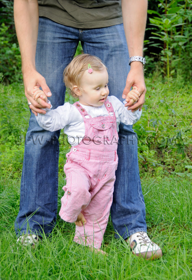 Cute little girl toddler learning walk father hand garden Stock