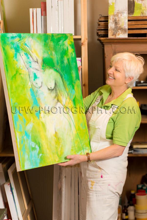 Female artist standing showing nude painting art studio Stock Im