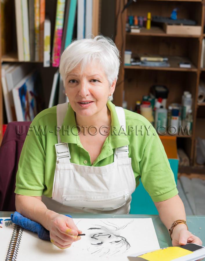 Female artist talking looking sitting sketching art studio Stock