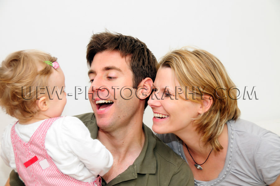 Happy young family of three smiling father mother toddler Stock