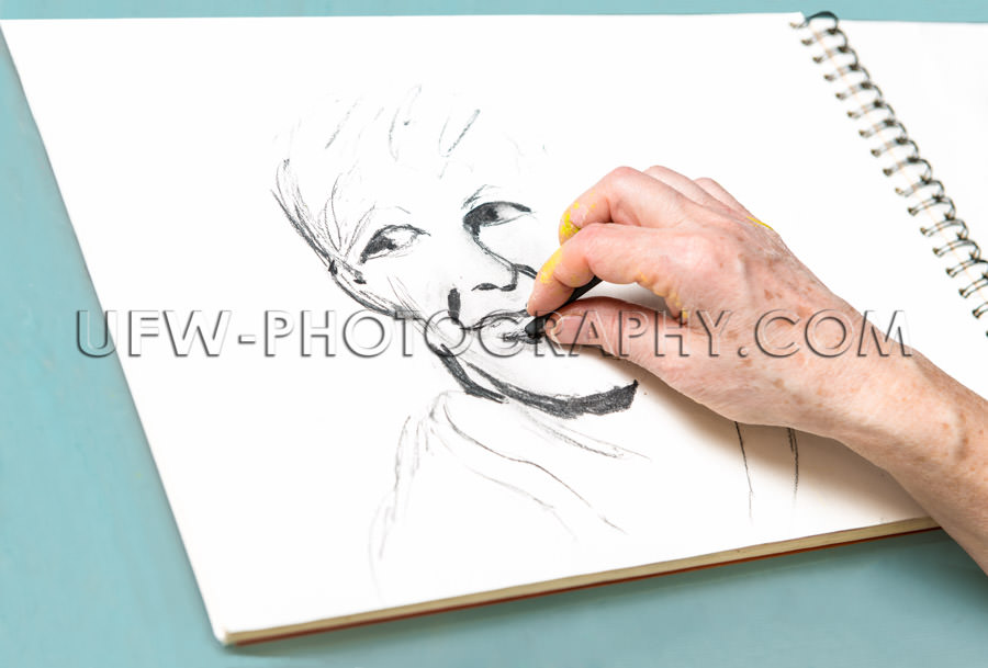 Human hand draws portrait charcoal pencil sketchbook Stock Image