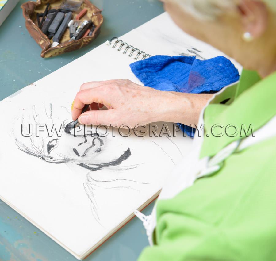 Look over shoulder woman artist draws portrait Stock Image