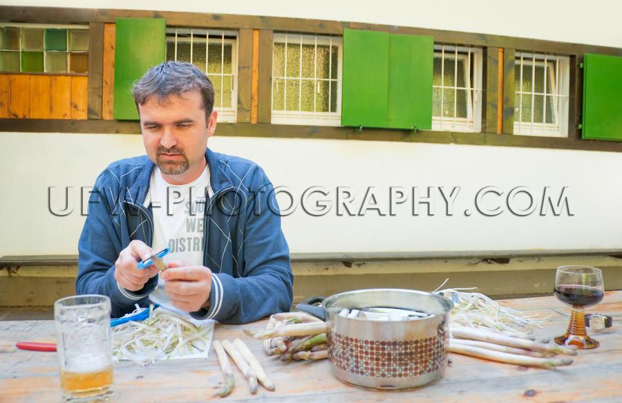 Man beard peels asparagus preparing outdoor household chores Sto