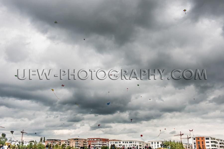 Many kites flying air kite-festival dark cloudy sky Stock Image