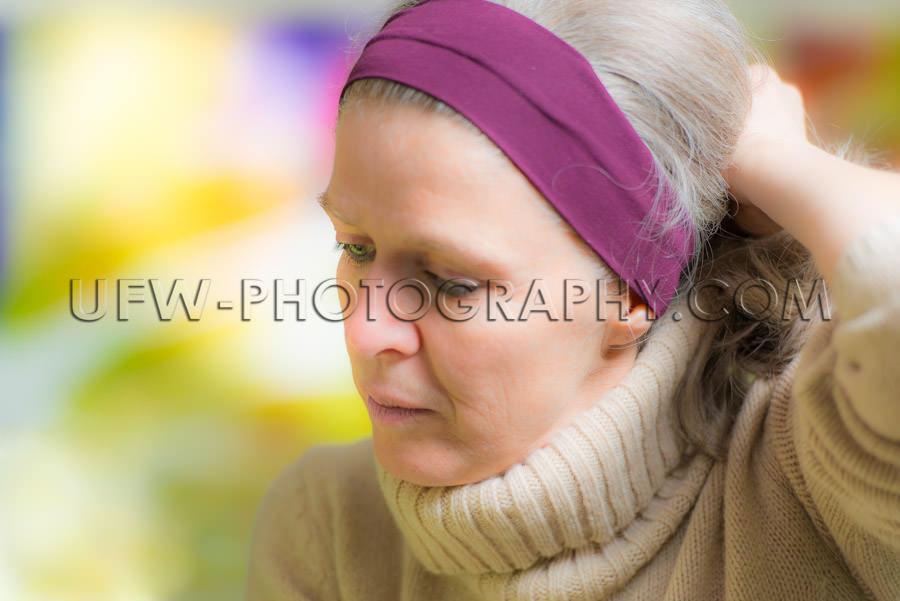 Pensive mature woman looking down portrait head-shot close up XX