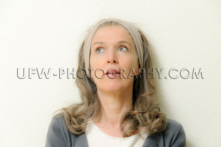Portrait of a mature woman, looking up, pensive - Stock Image