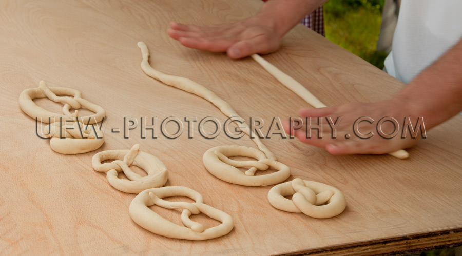 Pretzel making hands roll raw dough wooden table close up Stock