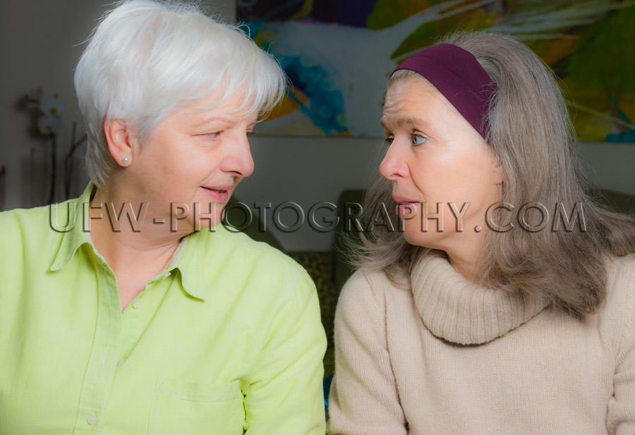 Two mature women talking looking face to face conversation Stock