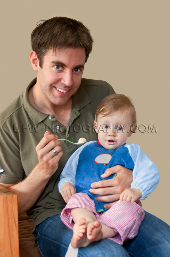 Young father feeding one year old girl toddler sitting laps Stoc