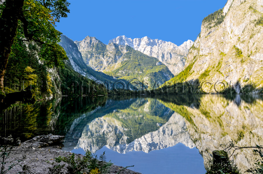 Mountain lake surrounded mountain-range dramatic reflection Stoc