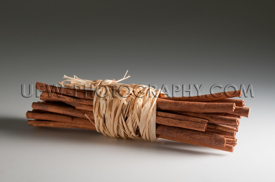Bunch of spicy cinnamon sticks tied up straw ribbon Stock Image
