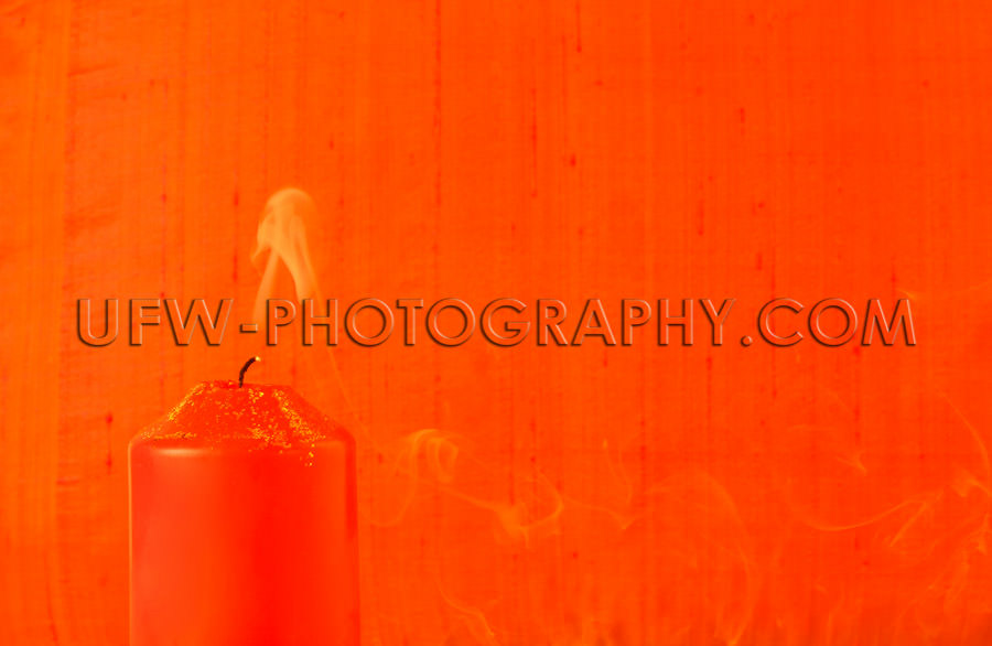 Extinguished light, red candle, golden glitter, smoke, textile b