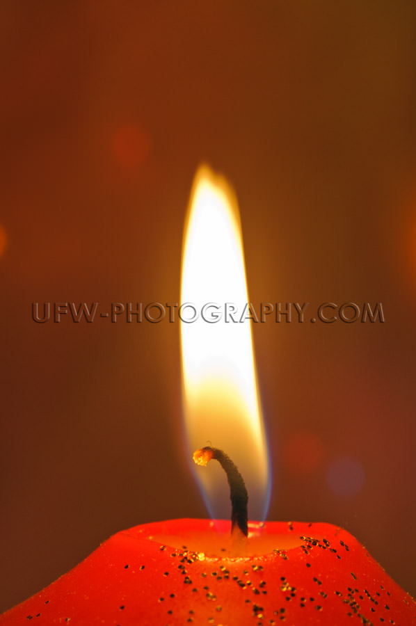 Macro of wick and candle flame, golden glitter, defocused backgr