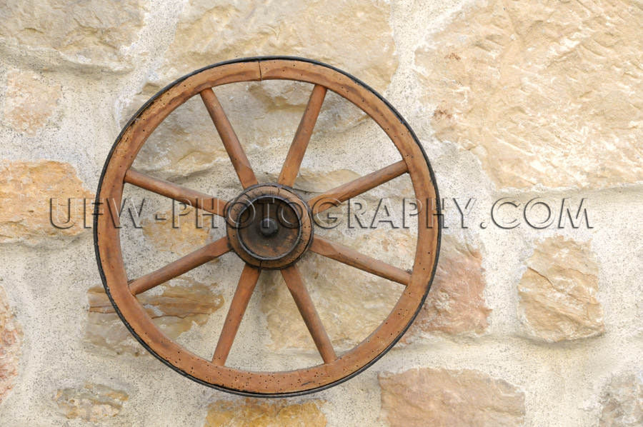 Old restored decorative clean wagon wheel stone wall close up St
